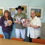 "June Lake Historical Society's Patti Henrichs, amateur film historian Ken Harrison, and librarian Vineca Hess welcome the ""Mono in the Movies"" DVD collection to the June Lake library."