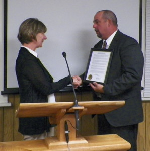 Judge Canfield's wife, Dori, receives proclamation from Bishop Mayor Jim Ellis.