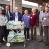 NIHD employees also gathered 39 gifts for the residents of Bishop Care Center. Shown with the cart of gifts, which the NIHD team pushed to neighboring BCC's front door, are from left to right, NIHD's Michelle Garcia, BCC Administrator Jay Caramba, BCC Director of Nursing Sue Uchendu, BCC Activities Assistant Cora Heeg, BCC Activities Director Ida Enger, NIHD CEO Dr. Kevin S. Flanigan, and NIHD's Kristen Bernasconi. Photo by Barbara Laughon/Northern Inyo Healthcare District
